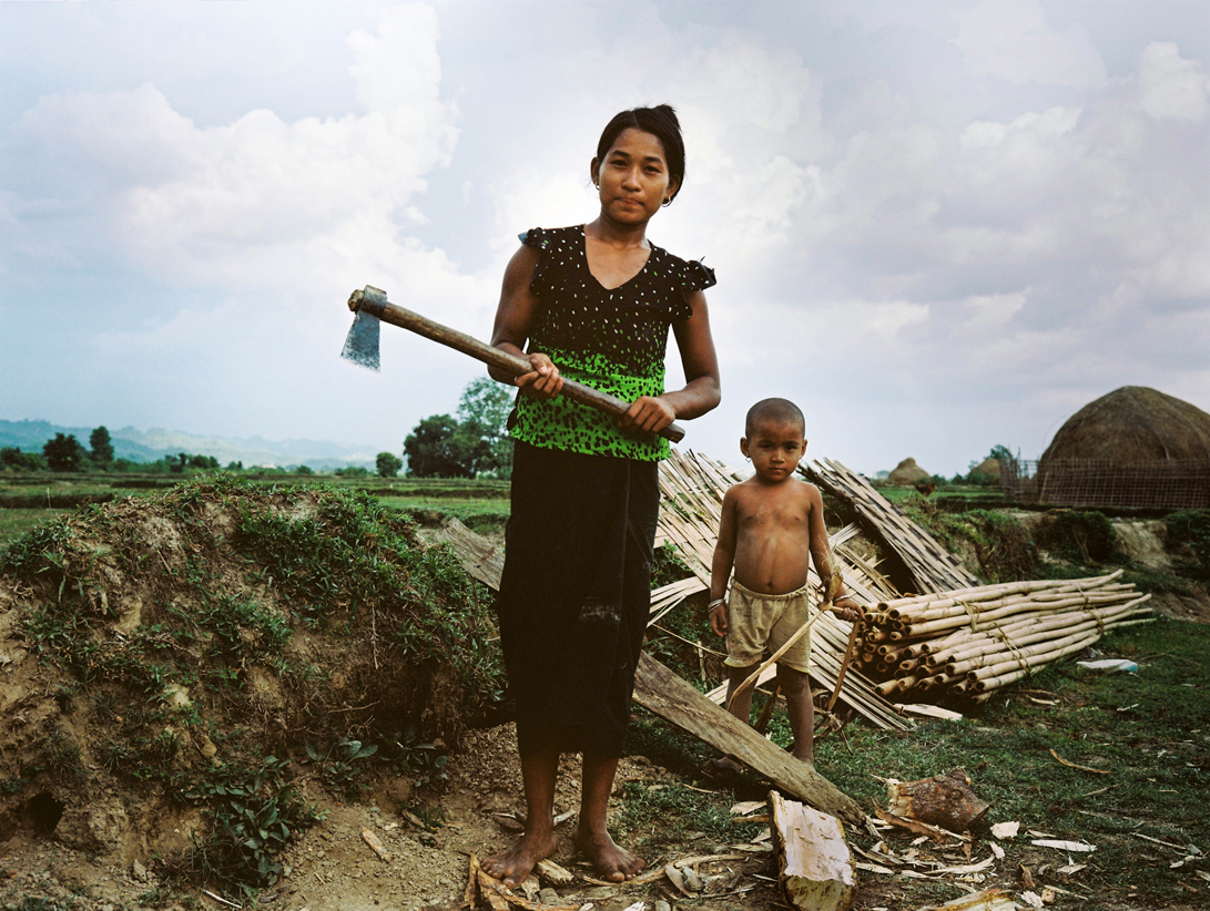 A Rohingya woman and child work in a field within a displaced persons camp in Myanmar. PIC: Ali MC