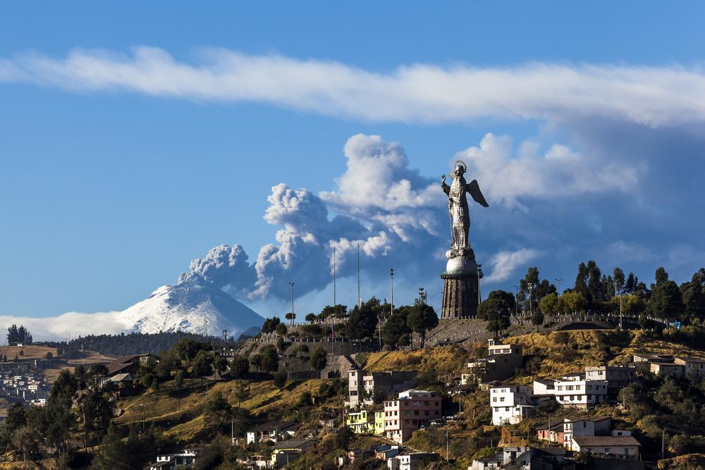 Cotopaxi volcano provides a stunning backdrop to Panecillo's Madonna seen from Quito, Ecuador.