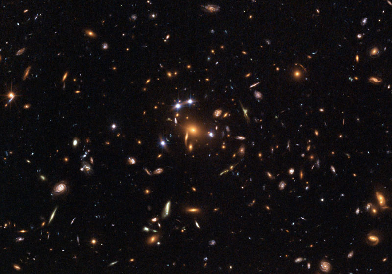 The gravity of a galaxy cluster warps and magnifies the light from a distant quasar. *Image courtesy of NASA and hubblesite.org